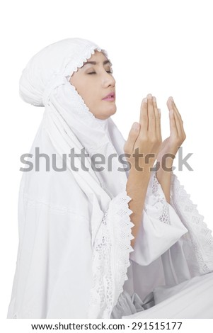 Pretty muslim woman wearing white clothes and praying on the GOD, isolated over white - stock photo
