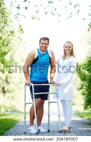Pretty nurse and male patient looking at camera in park - stock photo
