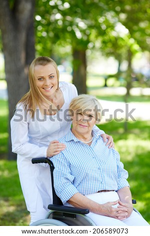 Pretty nurse and senior patient in a wheelchair looking at camera in park - stock photo
