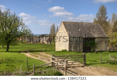 Pretty old barn on farm track through gate, Gloucestershire, England - stock photo