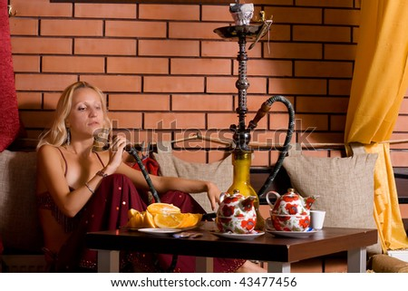 Pretty oriental dressed girl smokes a hookah - stock photo
