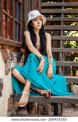 pretty pensive girl sitting on village staircases - stock photo