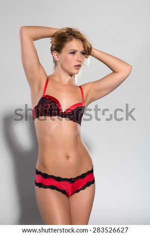 Pretty petite blonde in red and black lingerie - stock photo