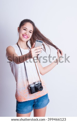 Pretty photographer girl taking selfie and smiling at camera - stock photo