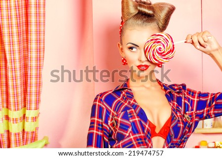 Pretty pin-up girl posing on a pink kitchen with a lollipop. Retro style. Fashion. - stock photo