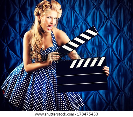 Pretty pin-up woman with retro hairstyle and make-up posing with clapper board over vintage background. - stock photo
