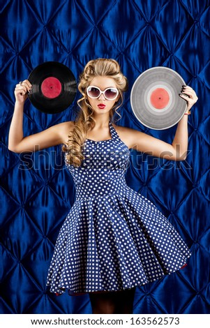 Pretty pin-up woman with retro hairstyle and make-up posing with vinyl record over vintage background. - stock photo