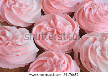Pretty pink cupcakes. Shallow dof, focus on the center cupcake. - stock photo