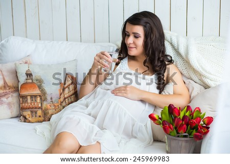 pretty pregnant woman drinking water while lying on a sofa at home - stock photo