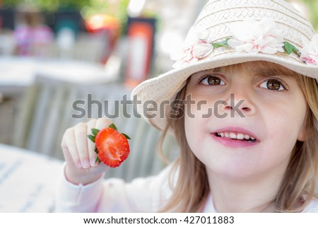 Pretty Preschooler Girl with Fruit. Female child holding strawberry. Childhood diet concept. - stock photo