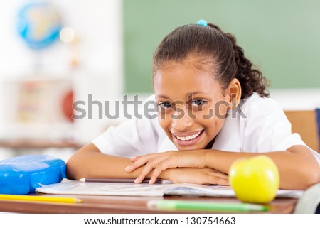 pretty primary schoolgirl sitting in classroom - stock photo