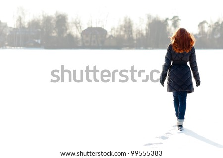 Pretty red haired girl walking on frozen lake and making footpath - stock photo