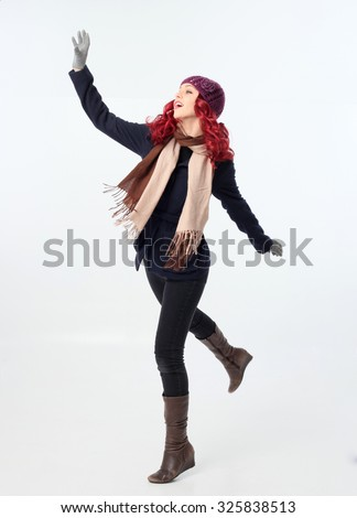 Pretty Red haired girl wearing winter coat, purple woolen hat and scarf, playing in snow, throwing snowball. Isolated on white background. - stock photo