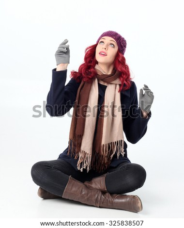 Pretty Red haired girl wearing winter coat, purple woolen hat and scarf, sitting cross legged.  reaching hands up to play in snow. Isolated on white background. - stock photo