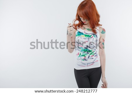 pretty red haired woman painting her T-shirt with paints.  - stock photo