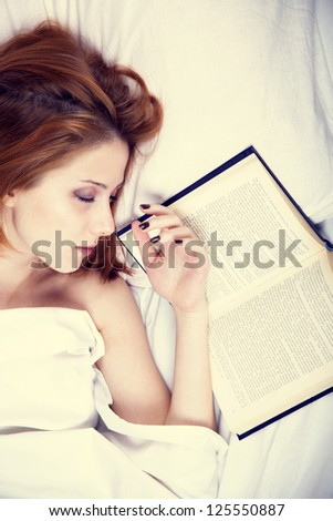 Pretty red-haired woman sleeping in the bed near book. Studio shot. - stock photo
