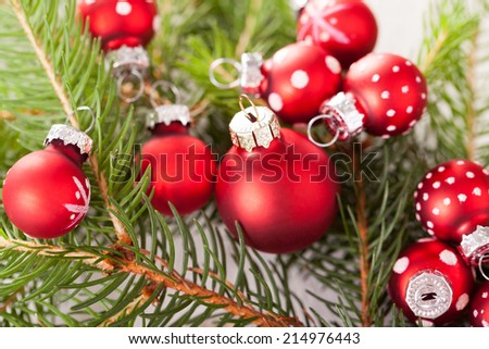 Pretty red polka dot Christmas bauble in a rustic Xmas seasonal background with burlap and scattered red ball decorations with fresh evergreen fir foliage - stock photo