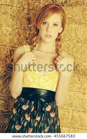 Pretty redhead country girl in hay - stock photo