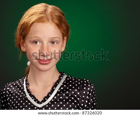 pretty redhead girl on green with copyspace - stock photo