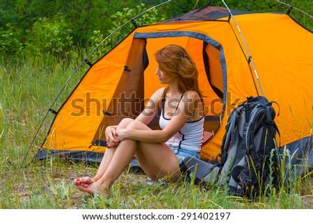 pretty redhead girl sit near a touristic tent - stock photo