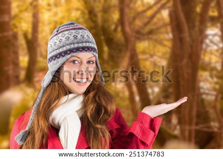 Pretty redhead in warm clothing against tranquil autumn scene in forest - stock photo