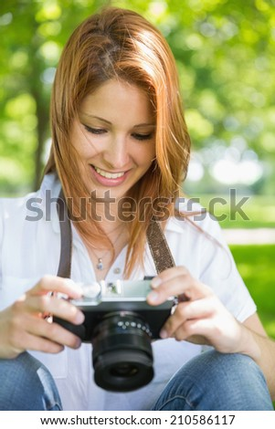 Pretty redhead looking at her camera in the park on a sunny day - stock photo
