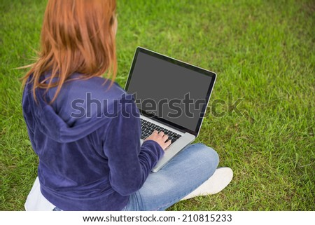 Pretty redhead relaxing in the park using laptop on a sunny day - stock photo