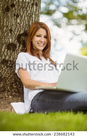 Pretty redhead sitting with her laptop in park on a sunny day - stock photo