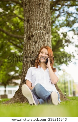 Pretty redhead smiling on the phone in park on a sunny day - stock photo