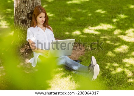 Pretty redhead typing on her laptop in park on a sunny day - stock photo