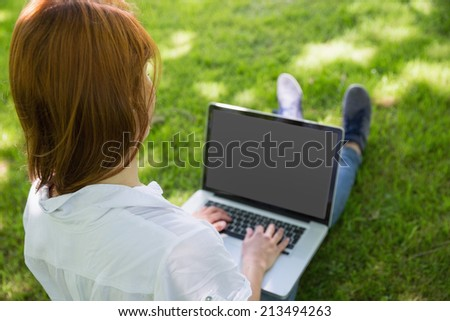 Pretty redhead using her laptop in the park on a sunny day - stock photo