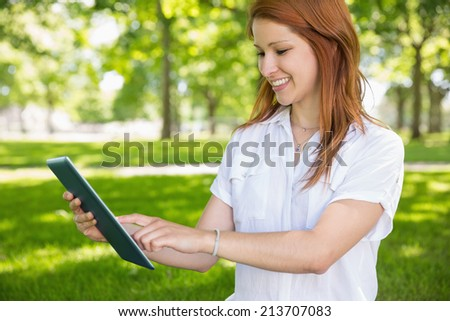 Pretty redhead using her tablet pc in the park on a sunny day - stock photo