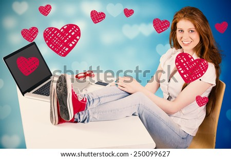 Pretty redhead with feet up on desk against valentines heart design - stock photo