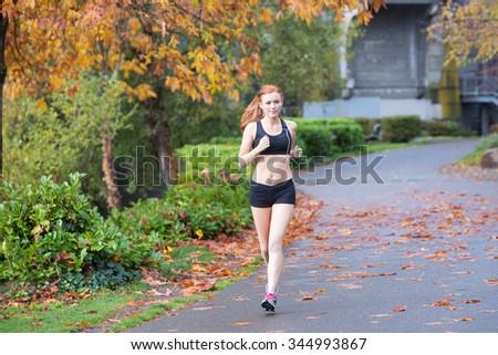 Pretty redhead woman running outside - stock photo