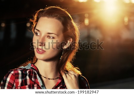 Pretty redhead women looking away at sanset backlit. - stock photo