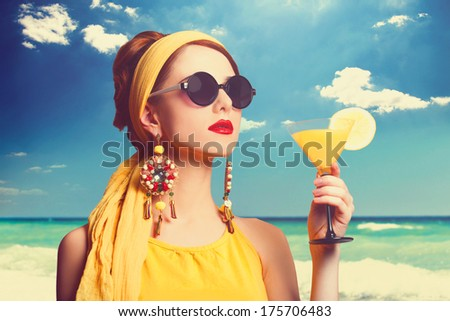 Pretty redhead women with cocktail on the beach. - stock photo