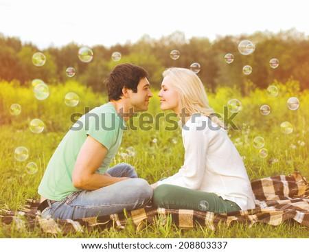 Pretty romantic couple in love having fun soap bubbles - stock photo