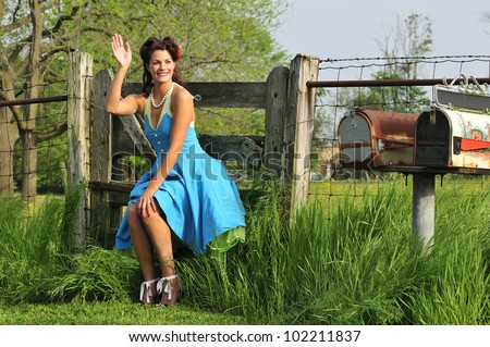 pretty 1940s pin up girl sitting around by a farm in the country side - stock photo