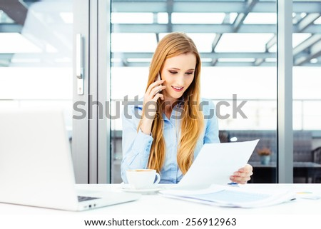 Pretty secretary sitting at a desk and talking on a mobile - stock photo