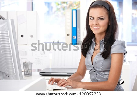 Pretty secretary sitting at desk, typing on computer, smiling, looking at camera. - stock photo