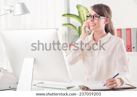 Pretty secretary talking on telephone and making notes - stock photo