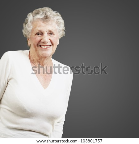 pretty senior woman smiling against a black background - stock photo