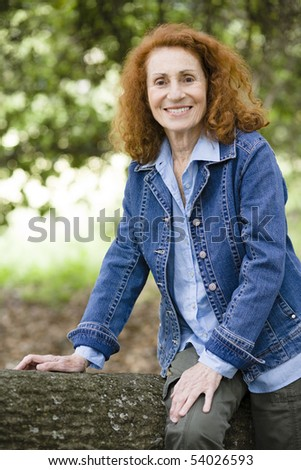 Pretty Senior Woman With Red Hair Sitting on a Treetrunk in a Park - stock photo
