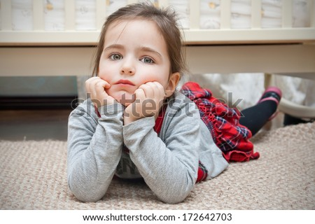Pretty serious little girl with big eyes lying down on the floor of the childroom - stock photo