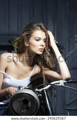 Pretty sexual young girl in white vest sitting on old fashioned motorcycle in garage on grey wooden wall background, vertical picture - stock photo