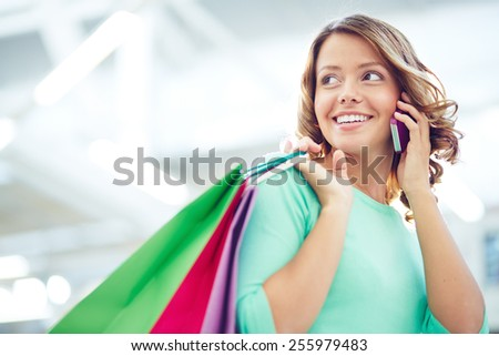 Pretty shopper with paperbags speaking on the phone - stock photo