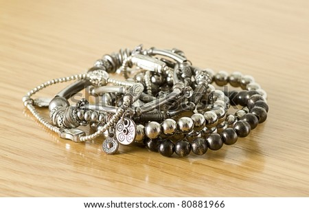 pretty silver bracelets isolated on a wooden background - stock photo
