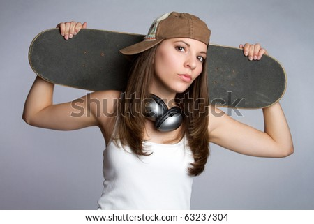 Pretty skater girl holding skateboard - stock photo