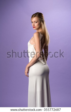 Pretty slender blonde woman in a long white gown - stock photo