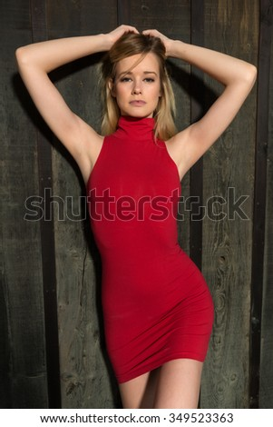 Pretty slender blonde woman in a short red dress - stock photo